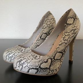 Fede sko i fake snake skin.  Hælhøjde: 11 cm  Plateau front: 2 cm  Lidt lim på indersiden af højre sko. Helt usynligt når den er på.   Normal i størrelsen.  Kun prøvet på.
