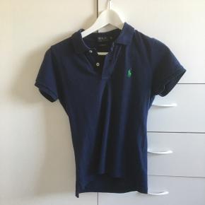 Blå polo fra Ralph Lauren. Skjorten er ikke brugt meget, og er i god stand. Den er lille i størrelsen. Køber betaler selv fragt!!
