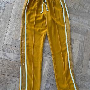 Birgitte Herskind bukser i karrygul. Lille udtræk på Venstre ben (billede 3), 100% polyethylene. Store i størrelse