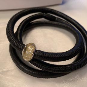 Fin sort læder armbånd fra Christina Watches med 1 charm.  Armbåndet har ikke været brugt.  Så man kan gå i smykkeforretningen og få klippet af armbåndet så den passer og de sætter låsen ordentlig på. ( det er ikke gjort, når man køber dem, da de skal tilpasses armen)
