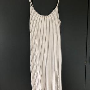 Kun brugt to gange. Fin lang, tætsiddende kjole, med slids i den ene side.