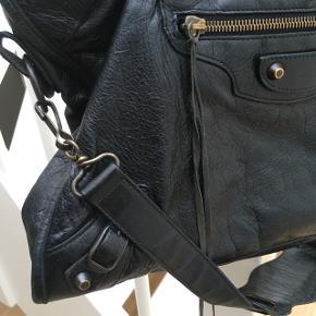 """BYD! Sælger denne Balenciaga City Bag i sort for min mor. Standen er god men brugt. Ingen huller i tasken eller på hjørnerne, kun almindelige brugsspor. Kvittering og spejl haves ikke længere.  Passer til 13"""" laptop. Kan sende flere billeder ved forespørgsel. MP: 5800,-"""