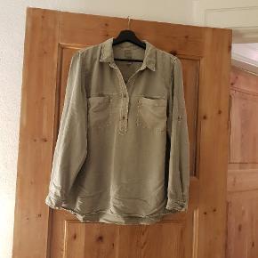 Fin skjorte i støvet grøn og løs pasform. Passes også af en small.