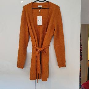 Lækker cardigan med bindebånd i taljen (aftageligt). Dejlig blød og i en smuk brændt-orange farve.  Sælges da jeg har alt for mange trøjer, og ikke har fået taget denne i brug.