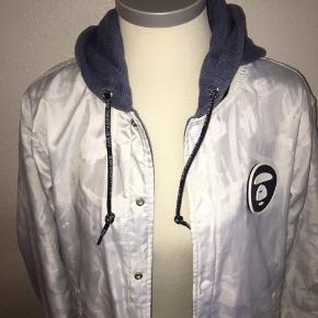Reversible jakke fra bape i størrelse large - men lille i størrelsen. Hvid og shiny polyester på den ene side og bomulds blå på den anden side. Med logo på ryggen samt hætte.