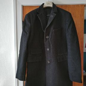 Flot klassisk frakke fra J. Lindberg. Flere lommer front og fine detaljer som knapper af horn og brug af læder. Lavet i mestendels uld. Str. Er 52 hvilket vil sige en L  Ny ca 3200 Mp 900