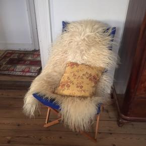 """Fin stol, der kan slås sammen. Som en flagermusstol. Der følger en pose i blåt stof med. Det blå betræk kan tages af og evt. skiftes. Der er skrevet """"max 75 kg"""" på den."""