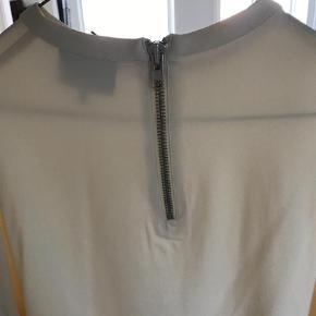 """Varetype: Bluse Farve: Råhvid Oprindelig købspris: 900 kr.  Super fin viskose bluse fra Ganni med lynlås øverst bagtil. Blusen er oversize / løs pasform. Jeg vil mene, den både kan passes af en small og en medium, da den ikke sidder kropsnært. Standen er helt som ny, men da jeg har haft den på en enkelt gang, ville jeg ikke skrive """"aldrig brugt"""". Jeg bytter ikke:) Hvis du bor i København og vil sparre fragten, kan vi mødes og handle."""