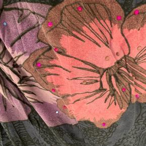 Lilla, pink, blå, lyselilla og detaljer med små sten på den ene side. Fantastisk flot nederdel