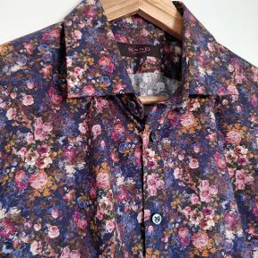 Flot skjorte fra Sand Copenhagen i str 40 Skjorten har et smart moderne blomster motiv. Skjorten kostede fra ny 1200 kr og har aldrig været brugt. Kommer fra ikke ryger hjem.