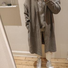 En varm og lækker jakke fra Moss Copenhagen i grå. Der er lommer i siderne og kan lukkes med bælte. Kun brugt én sæson.