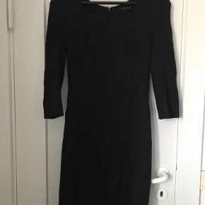 Kort, sort, tætsiddende, stretchy, klassisk kjole fra Tommy Hilfiger. 3/4 ærmer og lynlås hele vejen ned af ryggen.  Sender ikke - alt kan hentes på Emdrup St. i København.
