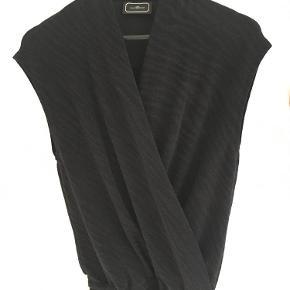 """Oprindelig købspris: 1900 kr.  Flot kort festkjole med metallic """"stribet effekt"""" med v-udskæring/ slå-om effekt. Kjolen strammes ind om taljen med elastik og fremhæver dermed ens figur. Længde til lige under knæ. Style: Nilcolla."""
