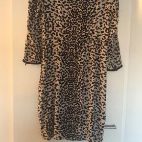 Leopardplettet kjole i beige og sort. Figursyet med lange ærmer. Længde over knæet.