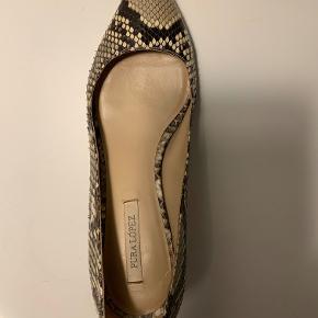 Smukkeste pumps i slangeskind fra Pura Lopez. Hælhøjde: 6 cm Brugt få gange. De har fået gummisål og hæl hos skomageren, for at beskytte skoen.