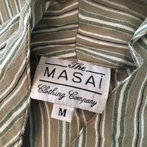 """Smuk bluse i stribet i bl a olivengrøn, beige.  Bred model.  Standen er """"næsten som ny"""". På billederne er den på en gine i str. medium."""