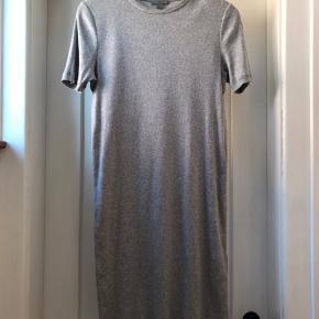 Ribstrikket t-shirt kjole 100% bomuld. Lys grå melange. Længde midt bag 91 cm. Bredde uden at strække 41 cm.