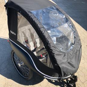 Næsten ubrugt Winther Dolphin XL cykelanhænger med plads til 2 børn.  Købt i 2015, men har max kørt 40-50 km. i alt. Har altid stået i garage.  Super lækker vogn i høj kvalitet med fokus på sikkerhed, som kan anvendes både som cykelanhænger og som klapvogn/løbevogn.  Der medfølger kobling, så den nemt og hurtigt kan sættes fast på cyklen, samt næsehjul, så den kan bruges som klapvogn.   Det er en rummelig vogn med ekstra højde, så der er god plads til børnene. Derudover er der et bagagerum, hvor der er plads til tasker og indkøbsposer.  Der er to justerbare 5-punktsseler samt komfortable sæder.