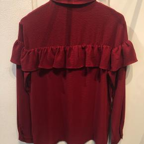 Fin skjortebluse i dyb rød med fine flæsedetaljer. Skjorten er størrelsessvarende.  Aldrig brugt, kun vasket.  BYTTER IKKE!