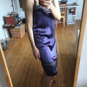 Sensuel lækker kjole i fed silke.  Lingeri/underkjole stil (men det er en almindelig kjole). En luksuriøs kjole i 'rich' materiale med fine hæklede detaljer ved kavalergang og knæ. Samt flæser som understreger det kvindelige og sovekammer-agtige. Oplagt til fest med stiletter.   1920'er og charleston stil.  Der medfølger silkebånd (i samme materiale som kjolen), som kan sættes i taljen; der er stropper i siderne af kjolen til båndet.  Kan også bruges som hverdagskjole om vinteren, med tynd rullekrave under, tykke strømpebukser, støvler - og 'bold' smykker!  Absolut aldrig brugt. I absolut perfekt stand.