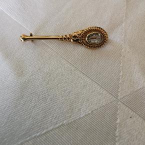 Smuk broche i 14 kt. Guld med en lyseblå sten. Ny pris : 2500 kr. Sælges for 1000 kr. Kan sendes med gls uden omdeling til 39 kr.