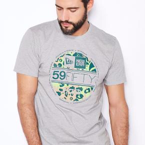 - 100% bomuld  New Era Cap t-shirt i grå med Jungle tema indeni deres kendte 59Fifty visor klistermærke på fronten, som normalt findes på deres 59Fifty cap modeller. New Era Cap er kendte for deres Caps, hvor den mest populære er 59Fifty eller Fitted som den også kaldes. Modellen er ikke justérbar i størrelsen, men kommer i forskellige størrelser.