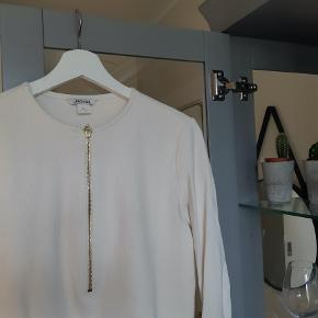 Hvid bluse med guld lynlås. Passes også af en Small.