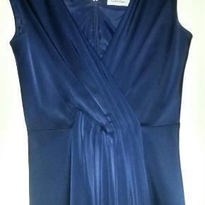 """Sælger min fine Calvin Klein kjole, da jeg simpelthen ikke får den brugt.   Skal lige nævne, at den i """"faldet/plisseringen"""" foran, har en lille bitte skramme/rift, som slet ikke ses, havde ikke set den selv, men damen på renseriet gjorde mig opmærksom på, at den var der, da de modtog kjolen, så det må jeg jo tro på? ;)   Har desværre ikke kunne fange den med kameraet.  Kjolen er 104 cm lang. Bryst: 2x41 cm. Talje 2x36 cm.   BYD :)  kjole Farve: Blå Oprindelig købspris: 800 kr."""