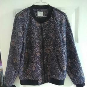 Mønstret jakke/overdel med lynlås og to lommer. Brugt et par gange i stedet for blazer eller cardigan.