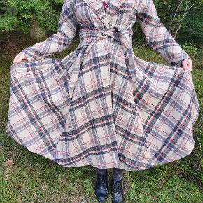 Fantastisk 50'er retro-frakke fra Love Your Look, London. Frakken er en swing-coat i 100% uld og med for I satin. Den lukkes med to hægter og et bindebælte. Har kun været brugt én sæson