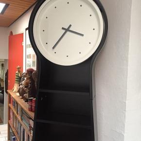 Fin sort reol med ur. Uret kræver batterier. Den måler 200 cm høj, 48 bred og 17 cm dyb.