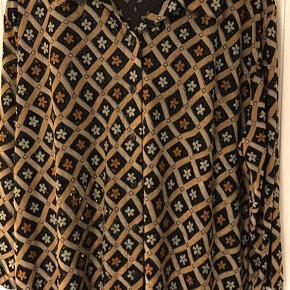 Retro bluse - mærket er 'X-fashion'.  Størrelsen hedder 54/56. Blusen er en smule gennemsigtig.  Med stræk. 75% viscose og 25% polyester. Brystvidde: 72 cm. X 2 uden at strække stoffet. Længde: 75 cm.