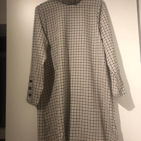 Løs, ternet kjole med smock-effekt ved ærmer samt hals. Har knapper på ærmerne. Brugt få gange.