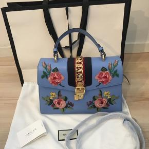 Varetype: taske Størrelse: Large Farve: Blå Forhandles til 21.000 i butikkerne   Gucci Sylvie Floral taske i den fineste lyseblå farve. Der medfølger alt på billedet, samt en skulderstrop, som er pakket ind i sin originale indpakning. Tasken er udsolgt på Guccis hjemmeside og er svær at få fat i, i netop denne farve.    Kom med et realistisk bud ☺️  Tasken kan ses i København K   Jeg bytter ikke og ved TS handel tilføjes et gebyr på 5%.