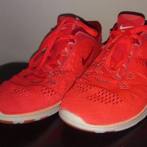"""Orange Nike Sko. Kan ikke huske, om de hedder Air eller Free. Men de har den kendte, superfleksible sål. Farven er orange - nogen ville måske kalde den tomatrød. Str er 40,5 - MEN jeg synes Nike er små i str (sammenlignet med fx Reebok, hvor jeg kan passe 39,5 og Adidas, hvor jeg bruger 40), så jeg synes mere de svarer til en alm. 40. De er ikke brugt voldsomt meget, men jeg angiver kun tøj/sko som """"Næsten som Ny"""" hvis det kun har været brugt 1-2 gange. Jeg har lige vasket skoene i vaskemaskinen og de ser ikke slidte ud. Man kan dog godt se nedenunder, at de er brugt - de skal nok lige skrubbes med en grøntsagsbørste el.lign. (-: De sælges for kun 175 kr alt inkl, da jeg bare ikke bruger dem mere. Jeg brugte dem mest indendøre til fitness nogle gange."""