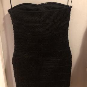 Smuk body-con dress. Den virker lidt korsetagtig Fine små pailletter får den til at glimte   Har stadig prismærke i
