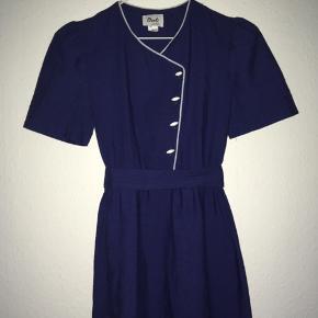 Smuk og meget special blå vintage kjole fra Barcelona. Den har hvide kantbånd ved krave og bryst og de fineste hvide knapper. Der er elastik i indsnittet ved taljen, og der følger et bælte/bånd med i samme stof som kjolen.