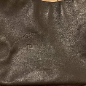 Mørkebrun Prada håndtaske i meget fin stand. Har et stort rum med magnet funktion og så et lille rum i tasken med lynlås (se billeder). Der er næsten ingen brugstegn.