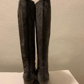 Lange grå ruskinds støvler i Str 37 med zip bagpå og lidt plateau sål foran  Brugt 2 x 1/2 dag, så fremstår som pænt nye Totallængde ca 48 cm og hæl ca 8 cm og sål foran ca 2 cm. Omkreds øverst bed skaft ca 36 cm og ved ankel ca 26 cm - målt udenpå. Ikke bred støvle! Nypris knap 2.000