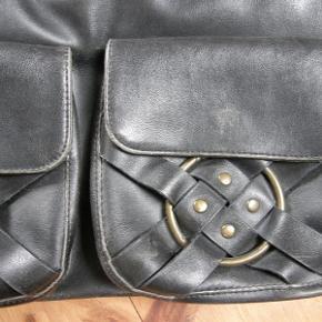 Superfed taske, som jeg bare næsten ikke har fået brugt. Mest bare fordi jeg ikke duer til tasker uden crossoverrem...  Tasken er i tykt, imiteret læder, med fede gyldne nitter og ringe, lynlås foroven og smarte magnetlukninger på de to lommer foran, så de er meganemme af knappe op og lukke i, når man lige skal have fat i pung, mobil etc. (-:  Farven er meget mørkebrun og den ser næsten sort ud.  Tasken er brugt meget lidt, og fremstår næsten som ny.  Mål: Længde: 48 cm, Højde: 29 cm.  Bunden er flad og rektangulær, så tasken kan stå selv, når der ellers er noget i den.  Sælges for 250 kr plus porto (TS-pakke m DAO 44 kr).  --- 0 ---  Se også alle de andre ting i sort, sølv, grå og guld, jeg sælger  taske stor skuldertaske Farve: Mørkebrun guld