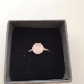 en sølv ring, i ægte sølv med en rosa sten på toppen. den er en størrelse xs. den er købt i catz