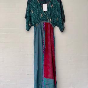 Sissel Edelbo kjole Model: Tithonia T-Dress kjole Farve: Multifarvet turkis grøn blå rød mm Størrelse: One size Købspris: 1200,-  Smuk kjole fra Sissel Edelbo Aldrig brugt, og stadigvæk med prismærke  Super smuk blød og lækker kjole.💞  Den smukke lange kjole er en one size, og passer til alle. Den har ærmer i 2/4 længde, et rynket elastisk bånd omkring taljen med snor til at binde taljen i en afslappet bue. Kjolen har et romantisk afslappet og bohemian look. Crossover-udskæringen giver en feminin og smuk silhuet.  Tithonia kjolen er perfekt til enhver lejlighed, og ideel til både dag- og aftentøj. Det feminine og alligevel enkle udtryk gør den perfekt til en dag i solskinnet med et par sandaler eller stylet med et par sneakers til hverdag for et afslappet look. Den smukke kjole er let at style til en aften ude eller med et par høje hæle til specielle lejligheder.  Kjolen er lavet af genanvendte sarier. Alle sarier er håndplukkede af Sissel Edelbo, og er, før de blev re-designet, blevet båret af en indisk kvinde. Kvindens og sariens historie viser sig i de unikke mønstre og små karakteristika. Ved at bære er stykke tøj fra Sissel Edelbo fortæller du historien videre.  Da stoffet er genanvendt, kender vi ikke den totale sammensætning af stoffet, som er håndplukket i Indien som en silke-mix. Der kan af samme grund forekomme små fejl i stoffet. De små fejl er en del af sariens charme og historie og betragtes ikke som reklamation.  Alle produkter fra Sissel Edelbo er unikke.  Dvs der kun findes den ene du ser her på billedet, og kun i den viste størrelse.  Dét gør din kjole helt unik - og et smukt og farverigt alternativ til andre kjoler.  LET THE STORY CONTINUE - FROM ONE WOMAN TO ANOTHER🌸💞🌸