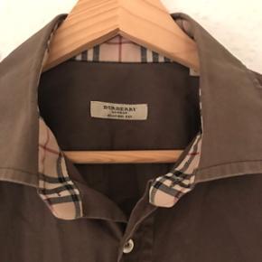 Cool ikonisk skjorte fra Burberry (London - deres næst dyreste kollektion før Prorsum) i mørke brun. Købt i butikken i London og kostede 1.550kr. Brugt enkelte gange omhyggeligt, medfølger ekstra knapper. Der står classic fit men den føles nærmest som en slim fit M/L