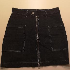 Denim nederdel med lommer og lynlås.  Det er en small, men den er lidt stor i størrelsen.