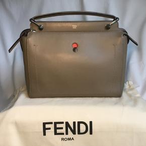 Sælger denne fine taske fra 2018-kollektionen. Tasken hedder 'Fendi.com' og kommer med en udtagelig, orange kuverttaske, som kan bruges for sig eller sammen med tasken. Kan også sættes fast uden på tasken for at give tasken et helt andet look. Sælges også med to skulderstropper, en i rosa/rød og en i beige som tasken. Farven er beige/nude, og den er i den absolut gode ende af 'som ny'. Den er brugt meget få gange. Nypris 15.000 dkk. Sender gerne referencenummeret og flere billeder. Mål 32x27x14 cm.