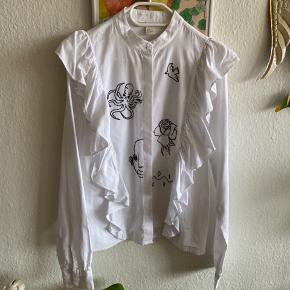H&M trend skjorte med flænser og broderi. Købt i Letland af en dame, som selv har broderet på skjorten. Nypris 750kr.
