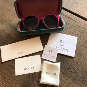 Gucci solbriller i farven fuchsia med glimmer  Str 54  Købt i maj 2015, for 2415kr  De har minimale brugsspor, dog har etuiet lidt skrammer hist og her af at ligge i min taske Der medfølger alle papirer, dustbag, etui og pudseklud