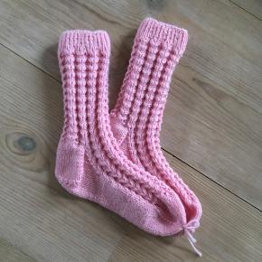 Håndstrikkede børnesokker med hulmønster i lyserødt garn. Foden er 16 cm.  80% superwash merino uld, 20% nylon  Prisen er fast.