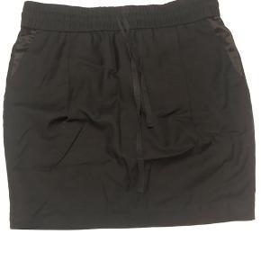 Sort nederdel med silkedetaljer ved lommer. Bindebånd og elastik i taljen.