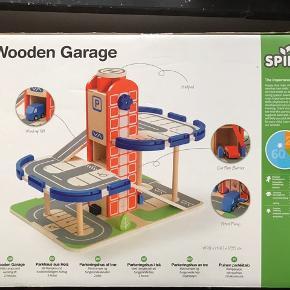 Ny og aldrig åbnet. Lækkert trælegetøj. Trægarage inklusiv 2 træbiler, elevator, ramper og benzinpumpe. Til børn +3 år. Fra Spire.